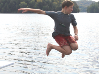 Tawingo College student jumping off diving board into Lake Vernon.